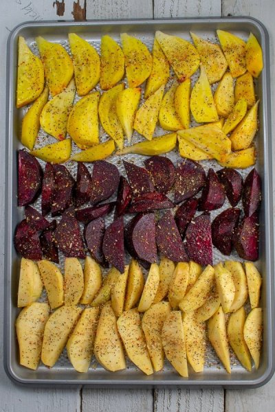 rutabagas and beets sliced in wedges on sheet pan