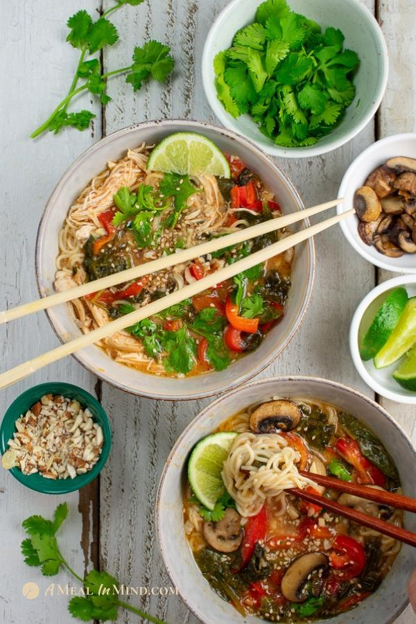 red thai curry ramen 2 ways in bowls with toppings overhead