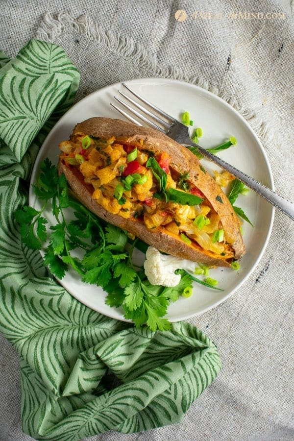 one thai massaman curry stuffed sweet potato on white plate with green cloth