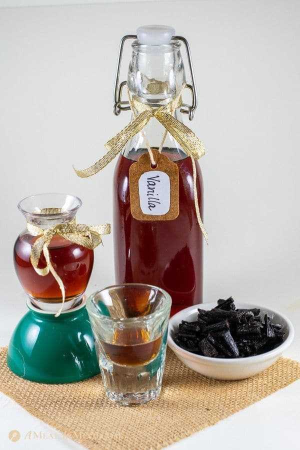 rich vanilla extract in glass containers and spent beans in small dish