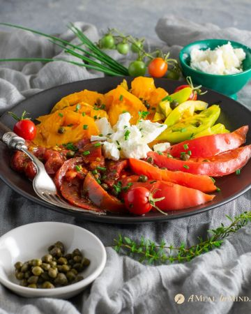 heirloom tomato salad with capers and feta on black plate