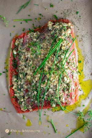 garlic herb salmon baked in parchment with sauce and herbs