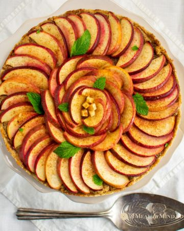 apple marzipan tart with almond crust on pie stand