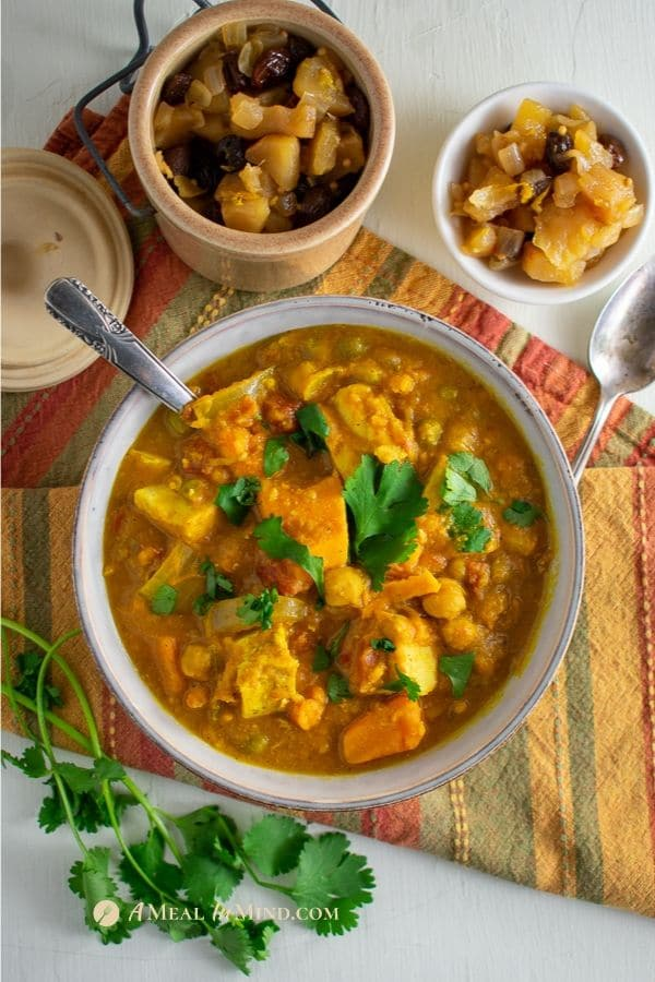 slow cooker sweet potato chicken curry in gray bowl on orange napkin