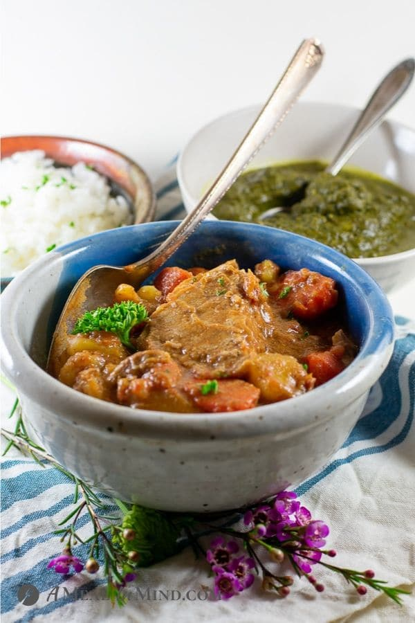 marrakesh lamb korma in bowl with side dishes