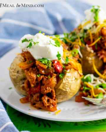Sloppy Joe Stuffed Potatoes on white plate with cheese and sour cream