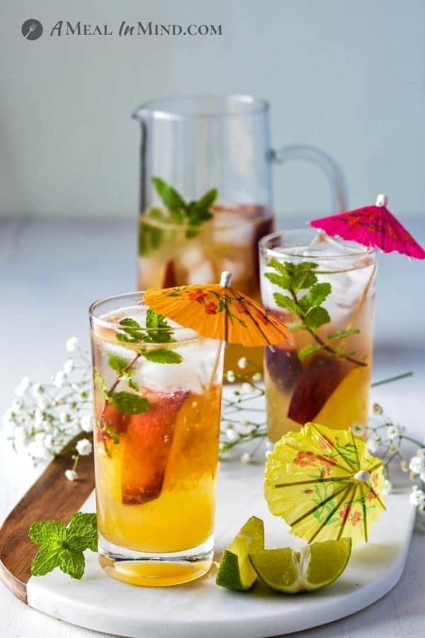 Peach-Ginger Limeade Mocktail in glasses and pitcher with umbrellas