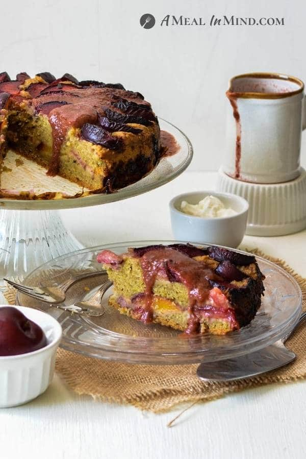 Plum Breakfast Cake with Plum Sauce on glass cake server with glass plates