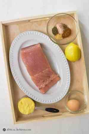 opah on white platter with an egg, seasonings, lemon and corn meal