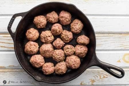 Paleo Pesto Meatballs in skillet after rolling