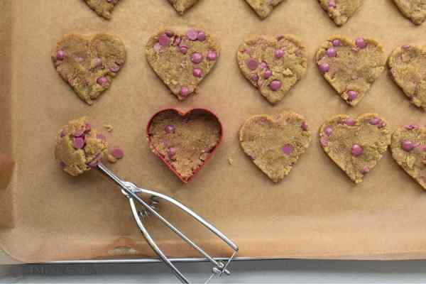 heart cookies in cookie cutter on baking sheet