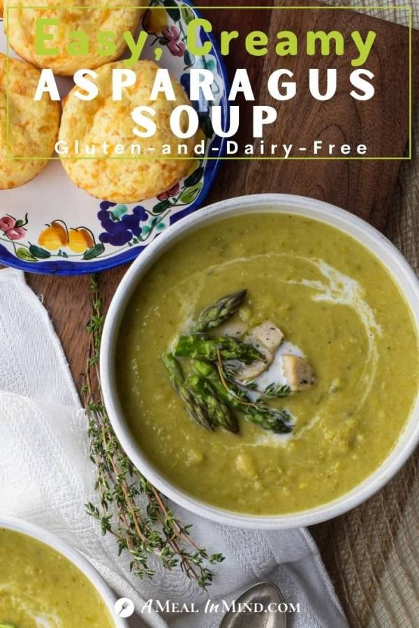 creamy asparagus soup in white bowl with cheese bread