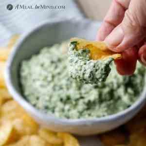 spinach artichoke dip closeup of potato chip