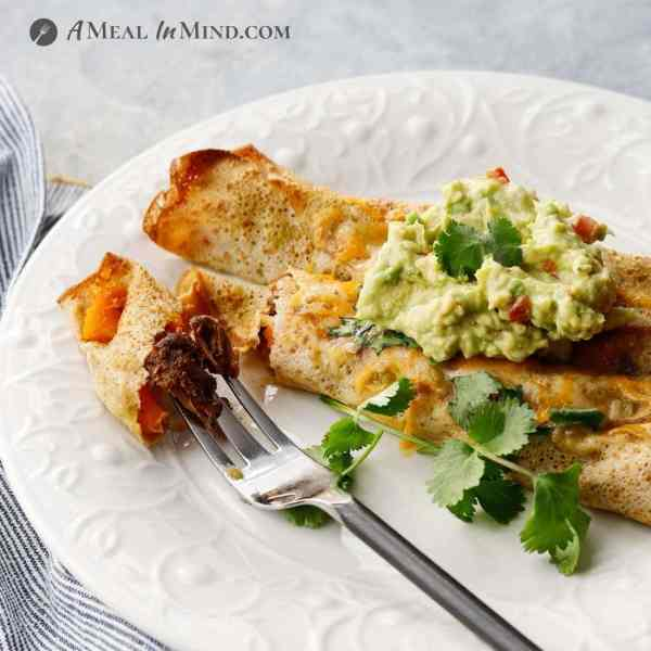 serving of carne asada enchiladas with guacamole on white plate