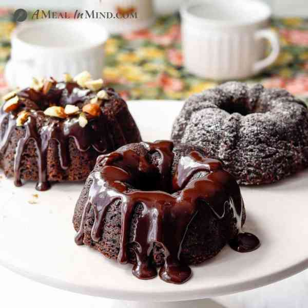 mini-bundt cakes on cake stand with teacups behind