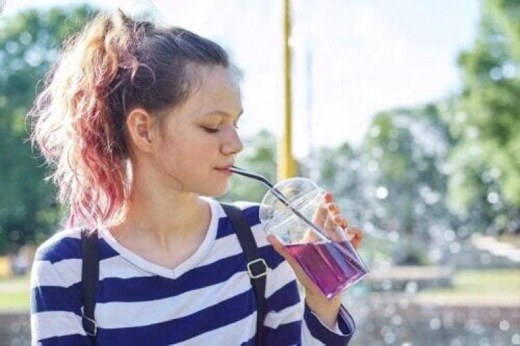 Une femme boit un liquide violet.