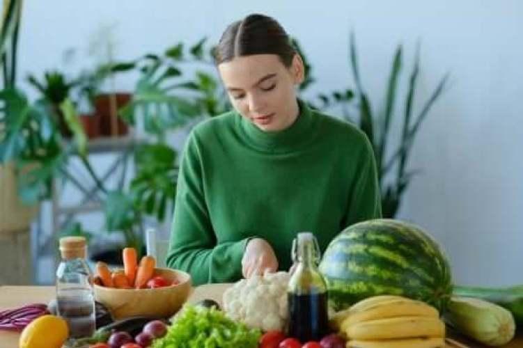 Une femme qui cuisine des fruits et des légumes.