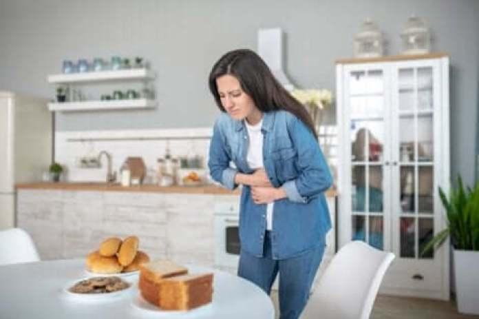 Une femme qui souffre de douleurs abdominales dues au gluten.