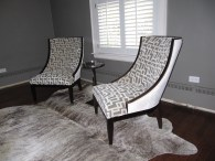 Contrasting fabrics on transitional chairs and a brindle cowhide rug create a cozy tete a tete