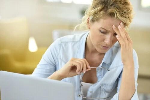 Mulher cansada diante de computador