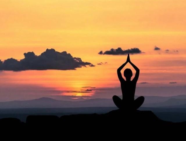 Mulher fazendo ioga no pôr do sol