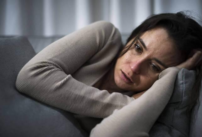 Mulher chorando deitada no sofá