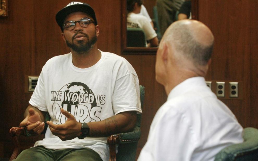 Dream Defenders Executive Director Phillip Agnew listens as Florida Gov. Rick Scott speaks in July 2013.