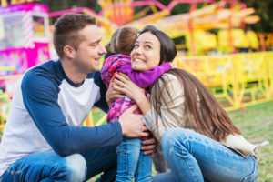 Cute little daughter hugging her mother, happy young family enjoying their time at amusement park, fun fair
