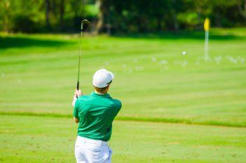 Golfer hitting golf shot on summer vacation
