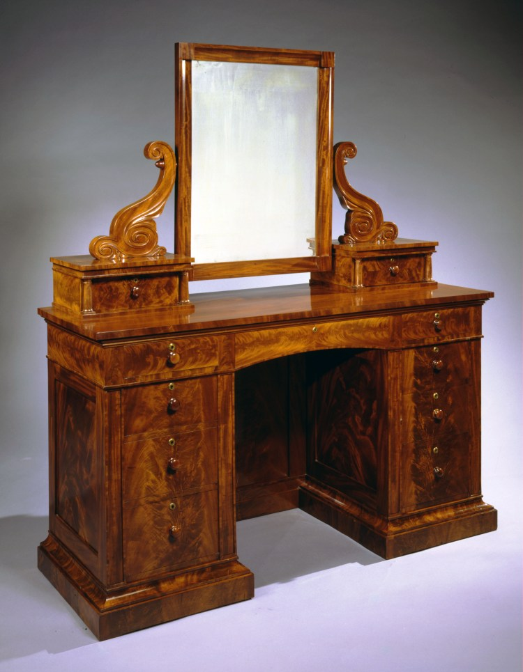 """Bureau with Attached Mirror: The coved rectangular dressing mirror frame suspended from flanking carved scrolled brackets on two short drawers with flanking colonettes set back on a knee-hole or pedestal-end case with four drawers in each pedestal-end with an arched central drawer, resting on a molded base. H 66¾"""", W 57½"""", D 21½"""""""