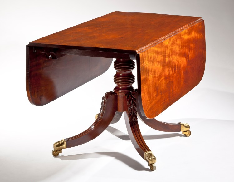 "Dining Table by Duncan Phyfe: Leaves down; The figured solid mahogany top with D-shaped drop leaves on a single ring-turned pedestal raised on saber legs with distinctive acanthus carving at the knees, terminating in elaborate brass toe caps with casters. H: 28¼""  D: 48""  W: 24""  W: open, 54"""