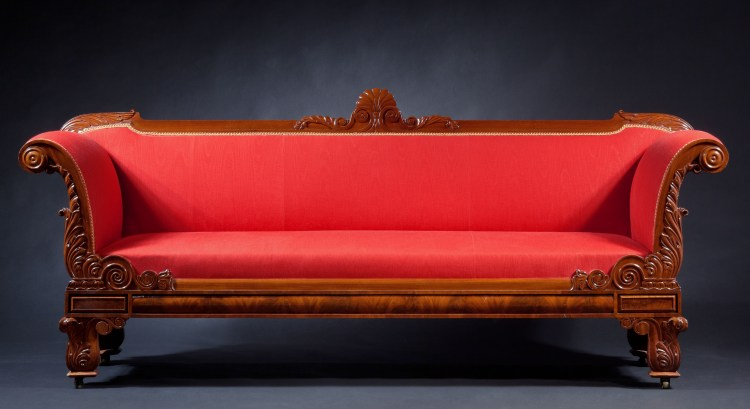 "Classical Grecian Sofa:  The molded crest rail centering a carved anthemion. The arms carved with acanthus leaves, lotus leaves and volutes terminating in molded bosses, and the bolection-molded and paneled seat rail terminating in rectangular paneled reserves above the legs, the legs with acanthus leaves and blind volutes raised on brass casters.  H: 37½   W: 89""   D: 26"""