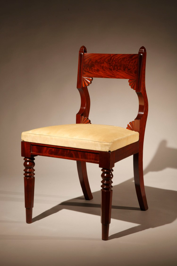 """Set of 12 Classical Dining Chairs by Bouvier: The slightly curved tablet crest rail veneered in highly figured mahogany, held between incised styles with pyramidal tops and distinctively curved stiles framing quarter-fan carving in the corners formed by the bottom of the crest rail and the top of the seat, above the upholstered slip seat, continuing as saber rear legs, the paneled seat rails supported in front by turned, faceted, tapering legs.  Six slip seats bear a period inscription, difficult to decipher, that looks like """"G  Bouvier"""""""