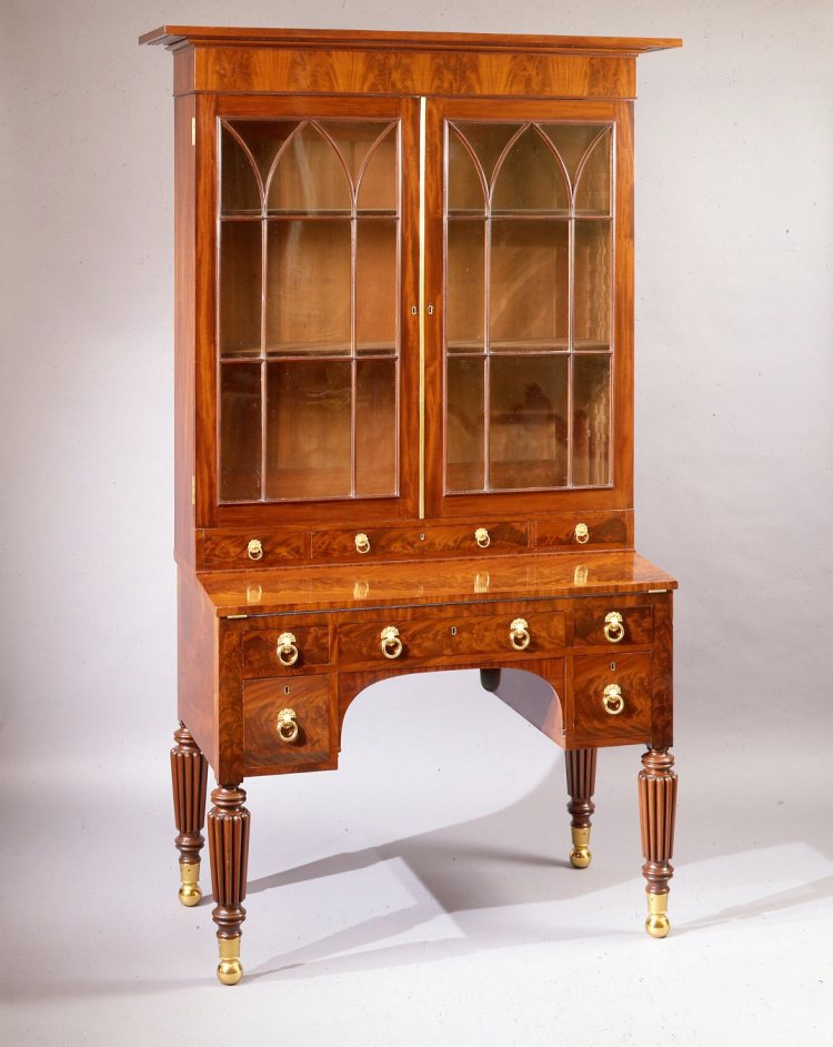 """Mahogany Federal Secretary and Bookcase: Comprised of two parts: The projecting pediment top above a veneered frieze above a pair of glazed cabinet doors with Gothic tracery opening to four fully adjustable shelves, over three short drawers with original brass pulls; the lower case with a hinged fold-out writing surface above a central long drawer flanked by short drawers above an arched knee hole flanked by square drawers all with original brass drawer pulls. The legs are turned and heavily reeded, terminating in brass socket ball feet.  H: 86"""" W: cornice: 51¾""""  case: 45""""  D: 23"""""""
