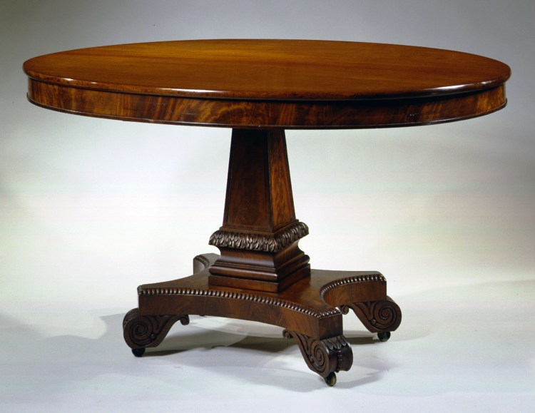 Oval Classical Library Table: The fixed oval top with a shallow skirt on a paneled pylon-shaped pillar with a molded and acanthus carved base resting on an abacus shaped plinth with spooling around the top edge, raised on carved volute-form feet with recessed brass caster wheels.