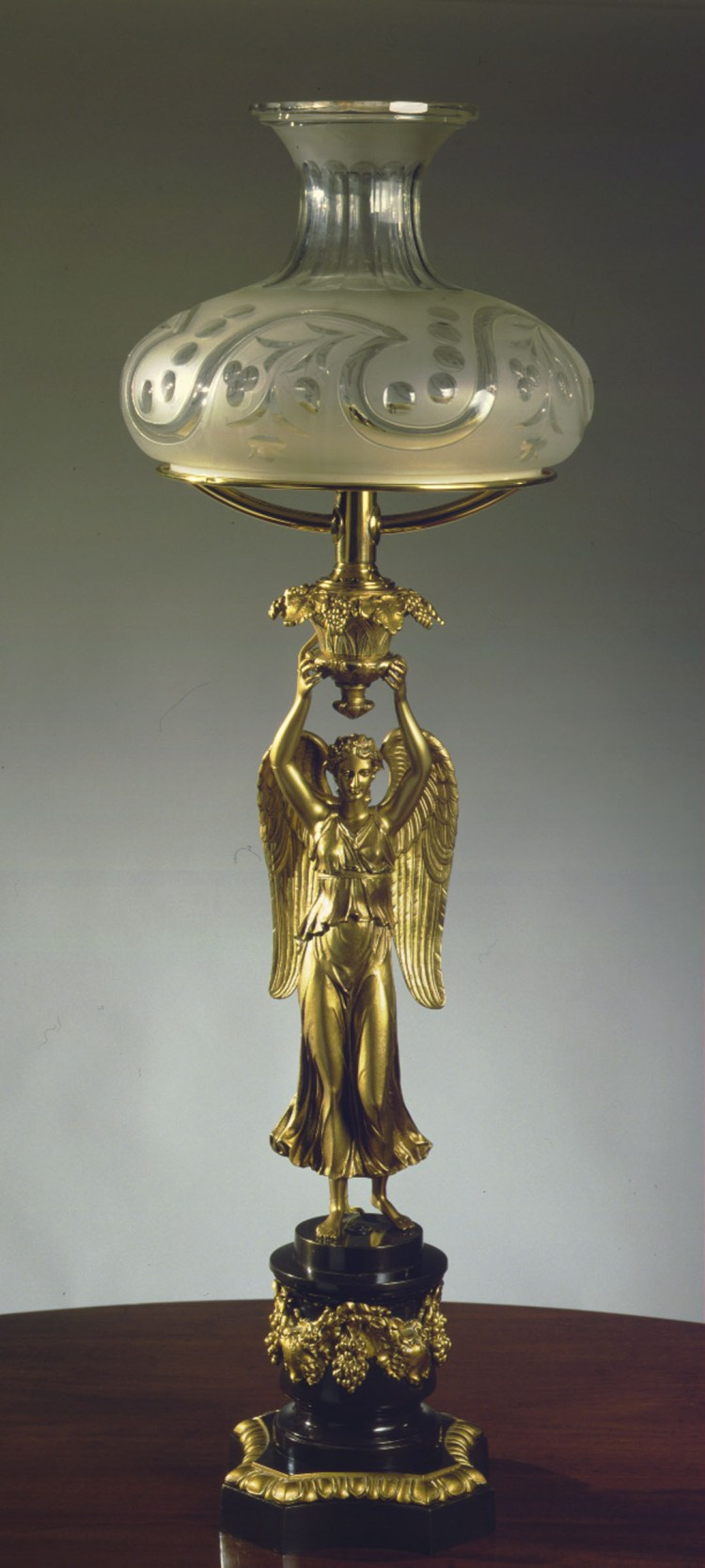 Figural Sinumbra Lamp: The blown and cut glass shade on a flattened doughnut-shaped font held above a figure of winged Nike, Greek goddess of victory, on a stepped cylindrical pedestal base decorated with swags and garlands on a molded polygonal base.  H: 37 ¼""