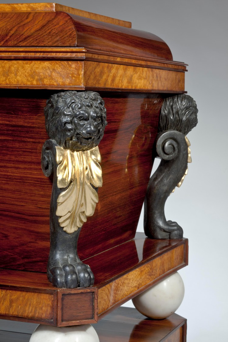 Rosewood and burl-wood sarcophagus CELLARET: Detail of carved lion's head scrolled monopodia with gilded acanthus leaf bibs.