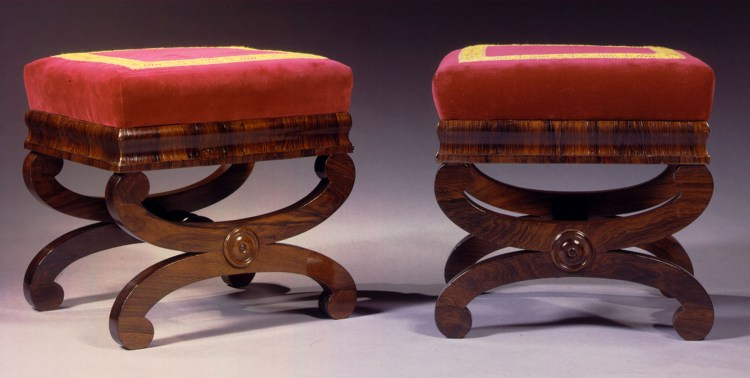 "Pair of Rosewood Curule-base Footstools: Each with a rectangular upholstered seat cushion in red velvet with red and yellow passementrie tape  bordering the seat, on a conforming molded frame raised on a curule base with a turned stretcher.  H: 15"",  W: 14½"",  D: 12½"" each"