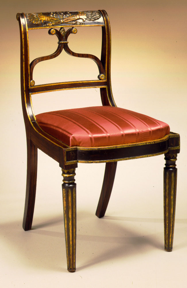 Carved, parcel-gilt and faux-grain painted Federal Chairs: Each of Klismos form with scrolled back with crest rail bas-relief-carved and gilded crossed, flaming torches, above a double cyma-shaped splat, with paneled stiles and an elliptic upholstered seat, the front legs turned and tapering with gilt flutes and capital elements.