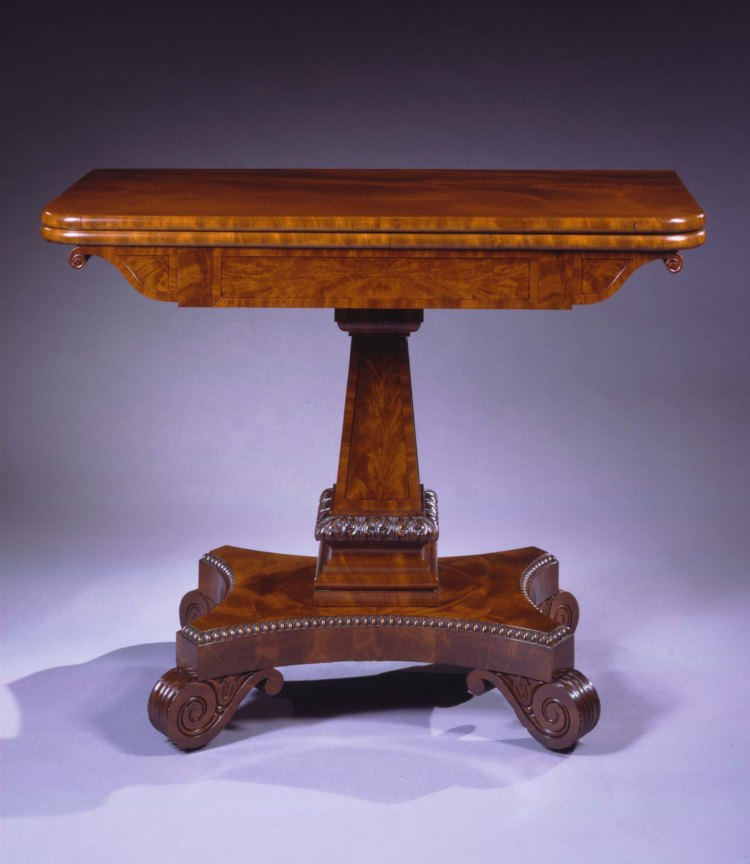 """Carved Mahogany Card Table by Isaac Vose: The oblong swivel top opening to a wood playing surface above an apron with scrolled ends above a paneled, pylon-shaped pedestal with acanthus carved collar at the base. The pedestal on an abacus-shaped plinth with spooling around the top edge, raised on scrolled feet with lotus carving on the sides, above recessed caster wheels. H: 29""""  W: 36""""  D: 18"""""""