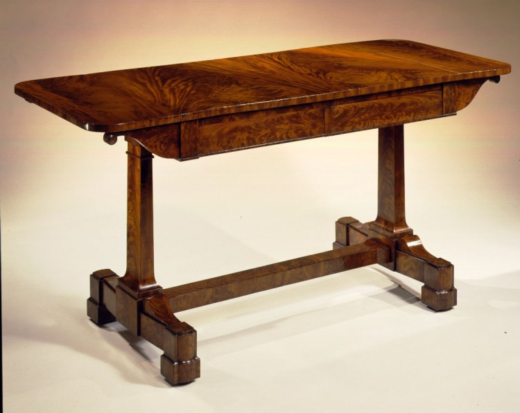 """Plain-Style Mahogany Sofa Table by Duncan Phyfe: The highly figured oblong top with short drop-leaves above a shallow case with two side-by-side drawers, a real and sham drawer on each side. Flanking the drawers on each side are bracket-shaped leaf supports terminating in rimmed disks that swing flush with the drawers and fold flush with the case when the leaves are down. The case supported by a trestle base with flat sided, highly figured vertical beams at each end that flair at the bottom as they meet the block base. They are connected to each other by a plain flat-sided stretcher. The legs extend out perpendicular to the beams, tapering to an elliptic terminal with a conforming blocked and molded foot, raised on recessed casters. H: 30""""  W: 40""""   open: 58"""" D: 26"""""""
