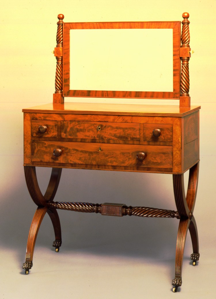 Federal dressing bureau with mirror has a rectangular mirror in a cross banded frame supported by reverse-twist rope-turned columns with ball finials over an oblong top with reeded edge on a conforming case with three short drawers over one long drawer flanked by inlaid dyes with Gothic arches, raised on reeded curule legs with carved paw feet and castors, the legs joined with a reverse-twist rope-turned stretcher centering a reeded rectangular block. Height: 55 inches,  Width: 37 inches,  Depth: 19 inches