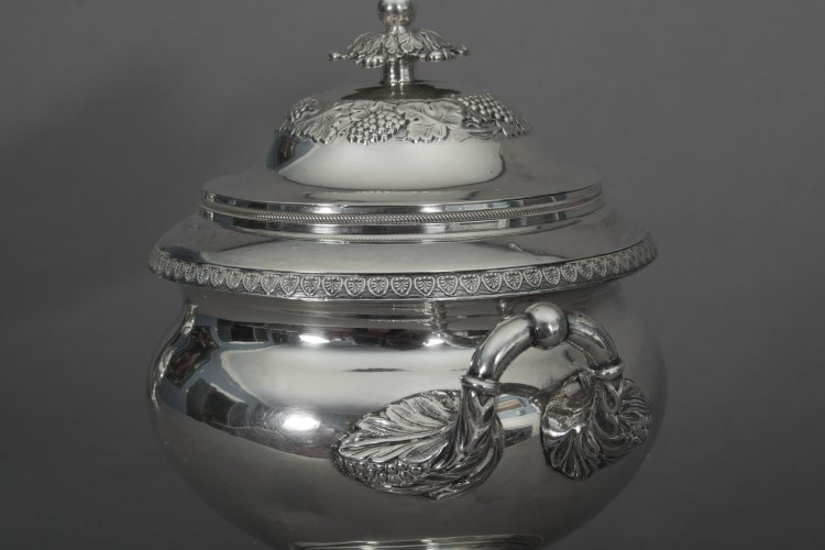 Silver Tea Service by Fletcher and Gardiner: Detail of lidded sugar bowl with leaf finial, repousse decoration, die stamped banding and handle.