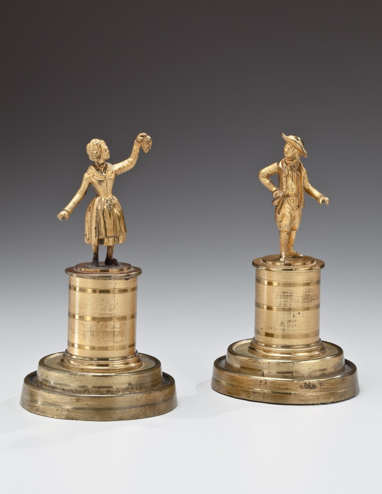 """Pair of Brass early 19th century figures, a man in a hat and awoman holding up a bunch of grapes, on cylindrical plinths and stepped bases.  Retaining original lacquered two-tone matte and burnished finish.   H: 6"""""""