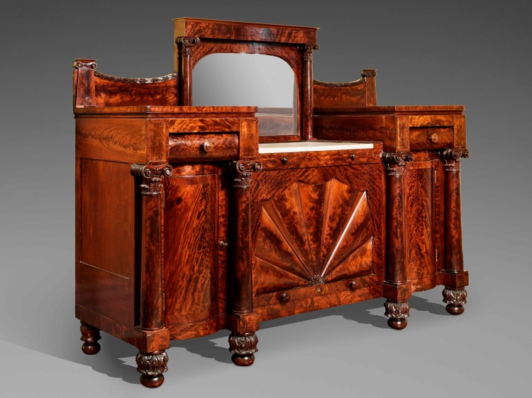 SIDEBOARD by John Needles: Three quarter view: The central back splash with mirror panel flanked by columns with carved Corinthian capitals, which are flanked by lower, veneered back splashes with carved garlands tracing the top edge. All above a pedestal-end case with a sunken center section with marble top, flanked by raised pedestal ends each with shallow bolection-molded drawers above convex cabinet doors flanked by veneered columns with carved Corinthian capitals and bases. The central section having a pull-out serving slide above a large garage-door type cabinet door with raised fan-shaped panels.  The case raised on acanthus carved ball feet.