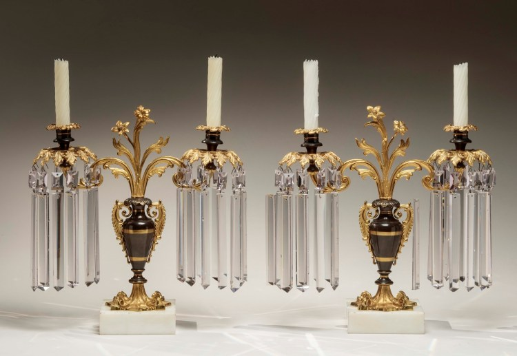 Pair of lacquered brass Girandoles each with two candle arms dripping glass prisms, supported by patinated urns issuing a central stand of flowers and leaves, each on white marble bases. Height: 16 inches.