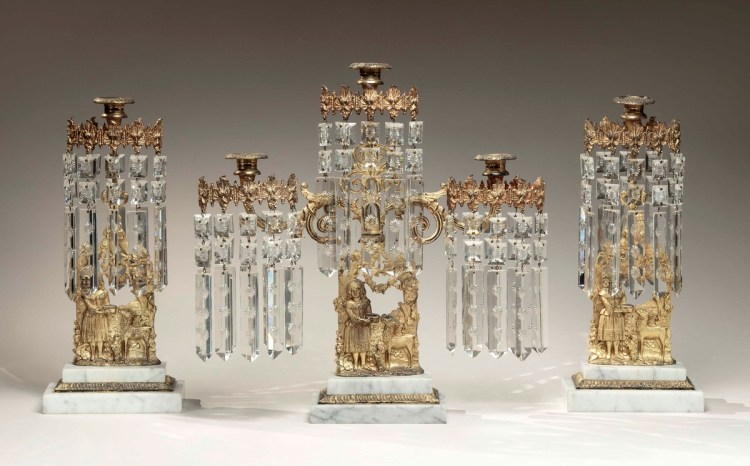 Mantel Garniture Set of Brass Girandoles; comprised of three parts with a central cast brass figural group with a child and a deer below three candle arms each with multiple cut glass prisms on a stepped white marble base, flanked by identical girandoles with single candle holders.