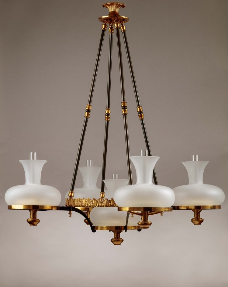 Simunbra Chandelier (lights off) having a foliate canopy above four pendant patinated rods supporting a circular cast foliate ring with four satellite extension rings holding sinumbra fonts with a fifth font suspended directly below the primary ring. Each burner tube bearing a label: MANUFACTURED BY/ H.N. HOOPER & CO./ BOSTON.