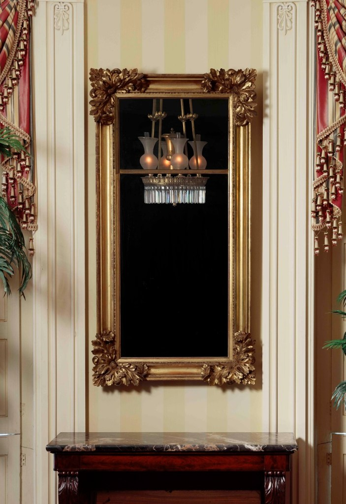 Gilt-wood pier mirror the glass  divided 1/3-2/3, framed by a gilt-wood cove frame with elaborate carved foliate elements. Designed to hang between doors or windows.