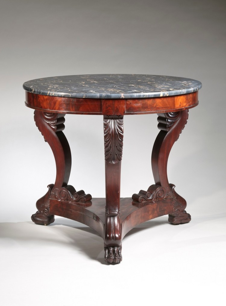"Carved mahogany guéridon with circular ""Egyptian"" marble top (black with white and gold figuring) above a conforming skirt supported by three scrolled cabriole legs with acanthus carving at the knees, resting on a tripartite plinth raised on carved lion's paw feet with recessed casters."